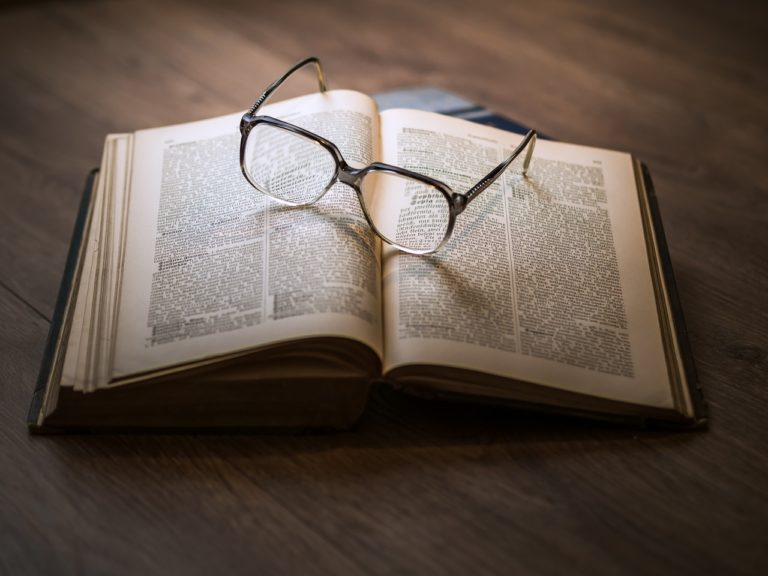 aufgeschlagenes Buch mit Brille